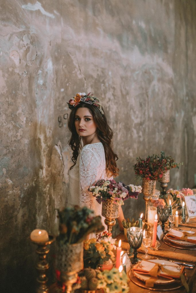Bride in an abandoned fabric behind a table full of candles and flowers
