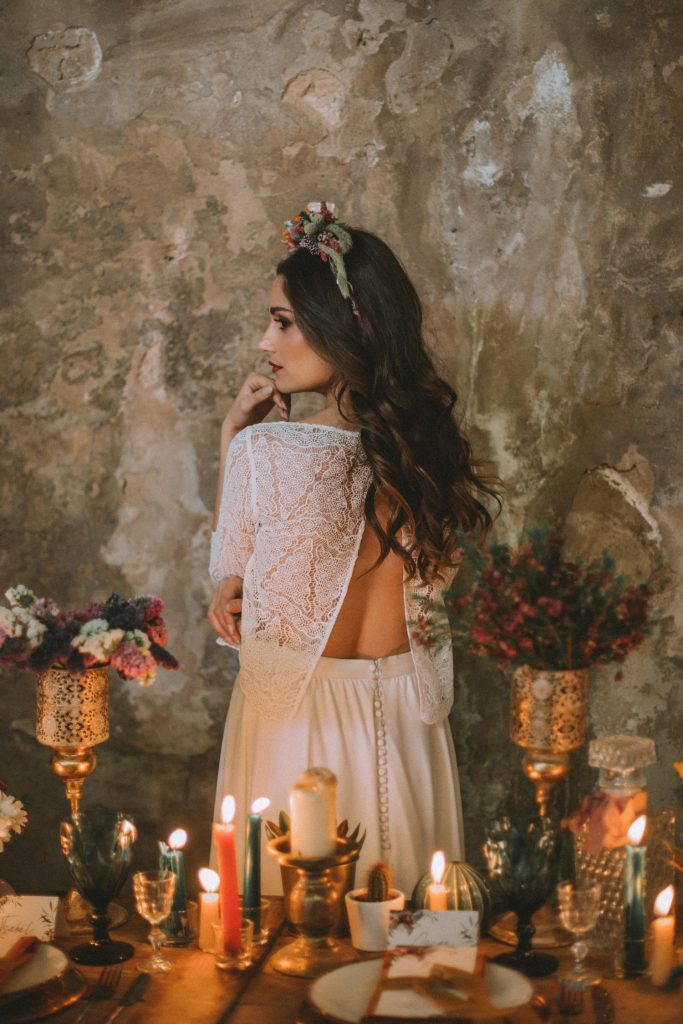 Bride in an abandoned fabric behind a table full of candles